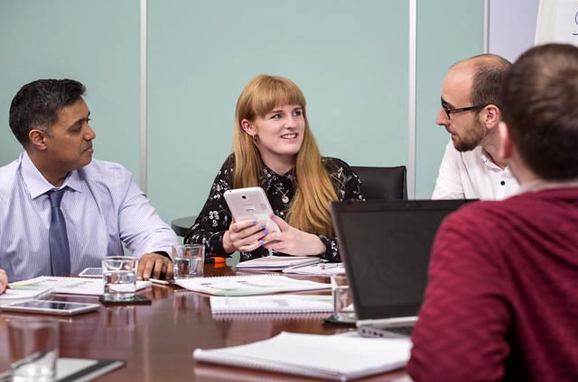 four people sat round a table in a business environment.