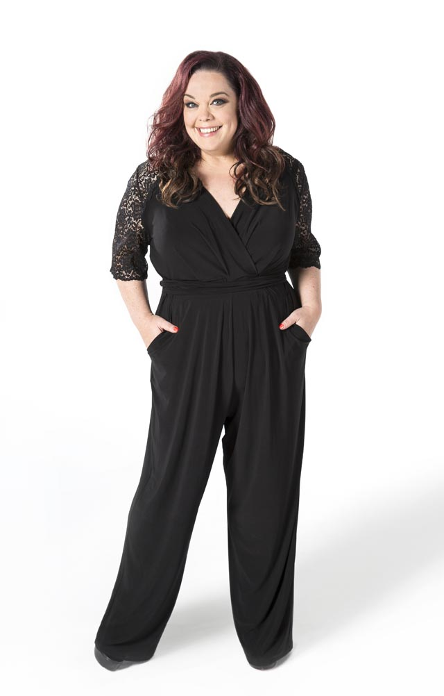 A woman stood on a white background wearing a black jumpsuit