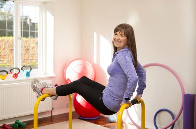 A woman exercising with gym equipment in a fitness environment.