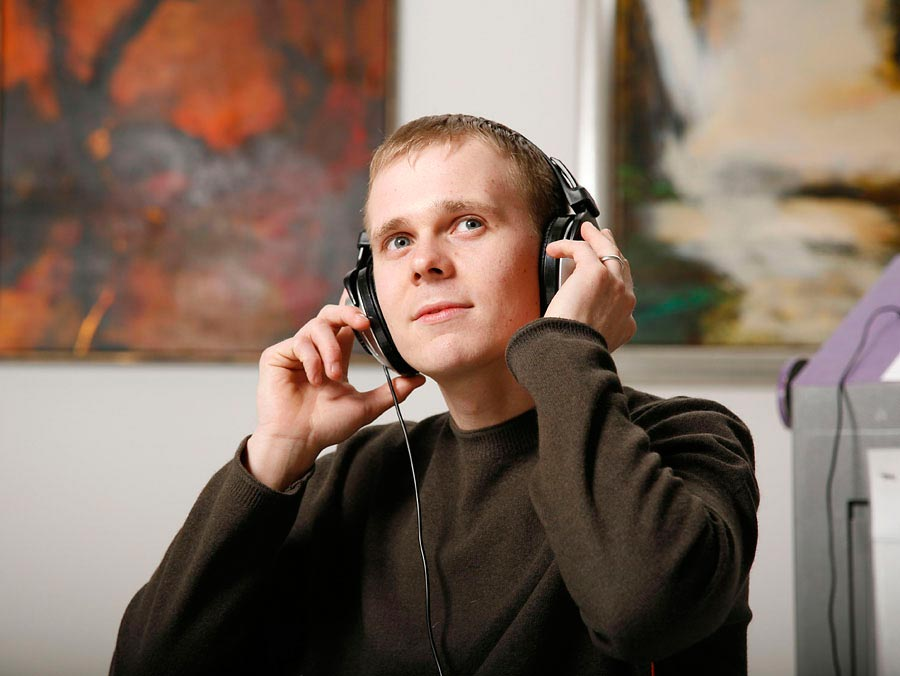 Image of a man listening to headphones in an art gallery setting.