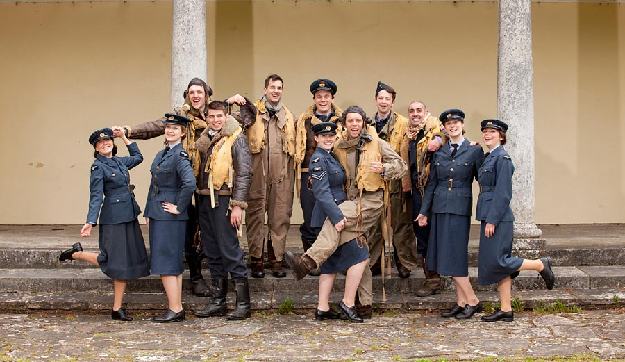 A group shot of about 15 actors dressed in 1940's RAF clothes.