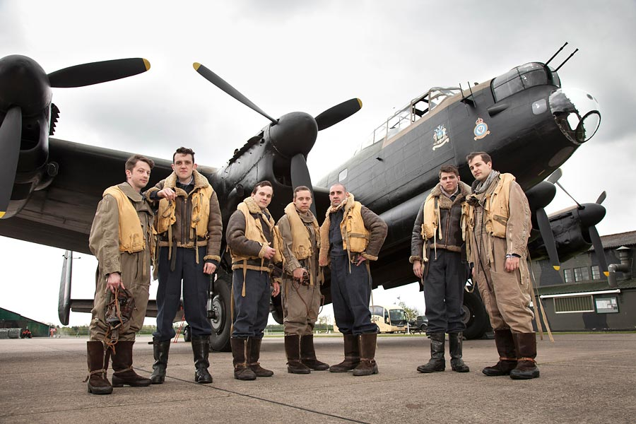 A group of actors dressed up in RAF geat from the 40's by a lancaster bomber aeroplane.