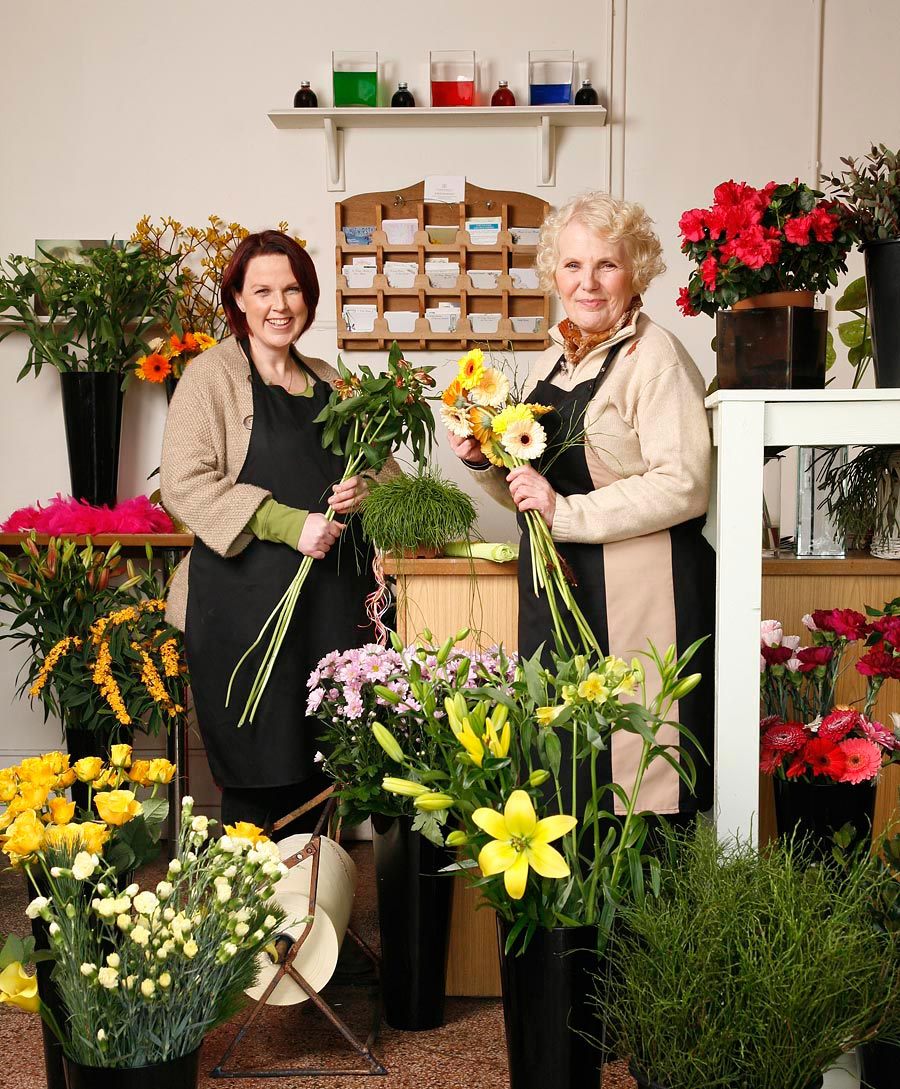 Two women posed in a florist shop.