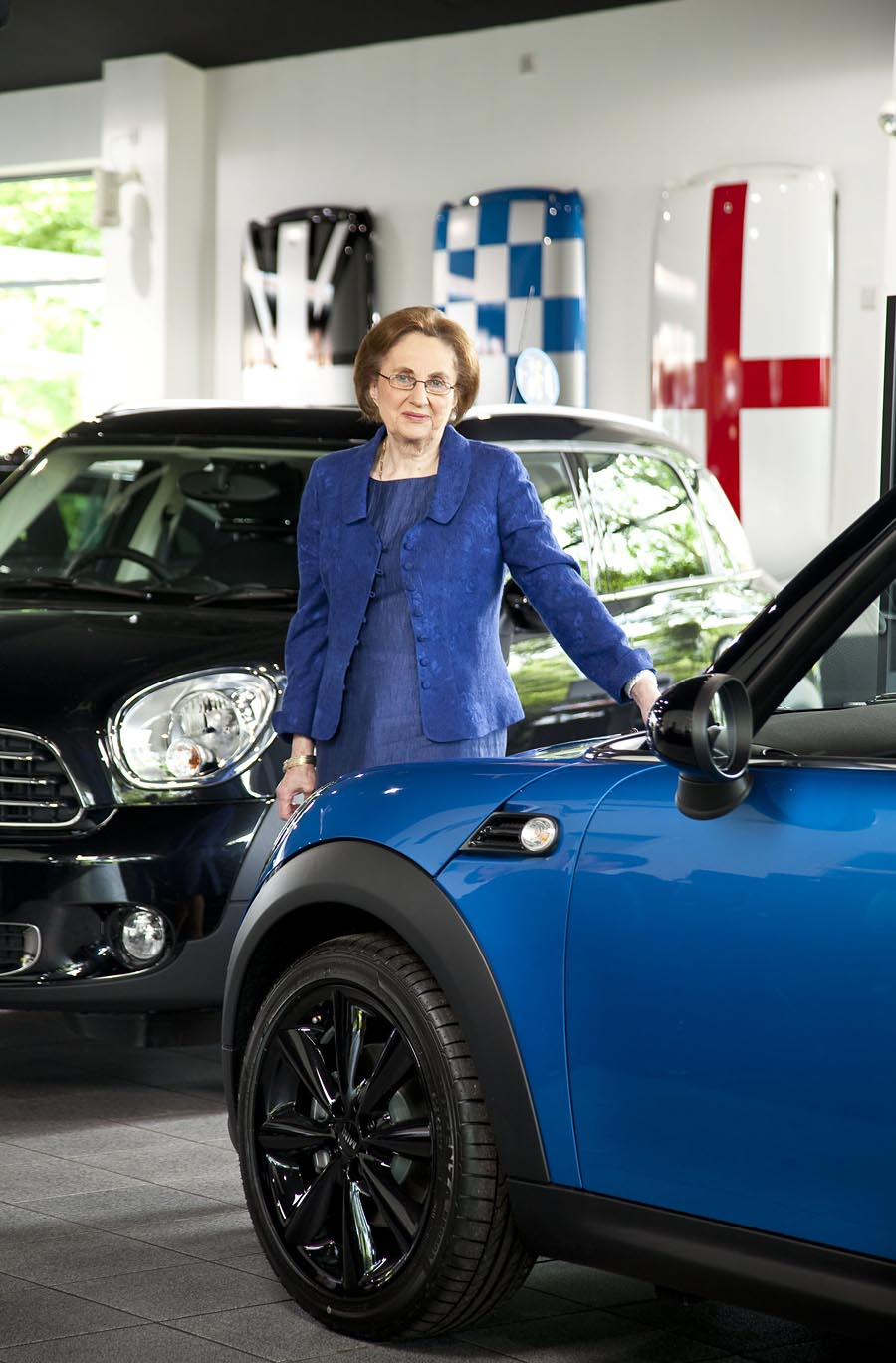 A woman dressed in blue next to a blue mini car in a car showroom.