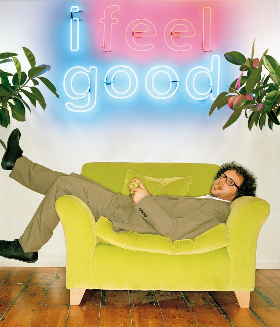 A man in a beige suit layed on a bright orange sofa with a grape in his mouth with a neon sign behind him that reads' I feel good'.