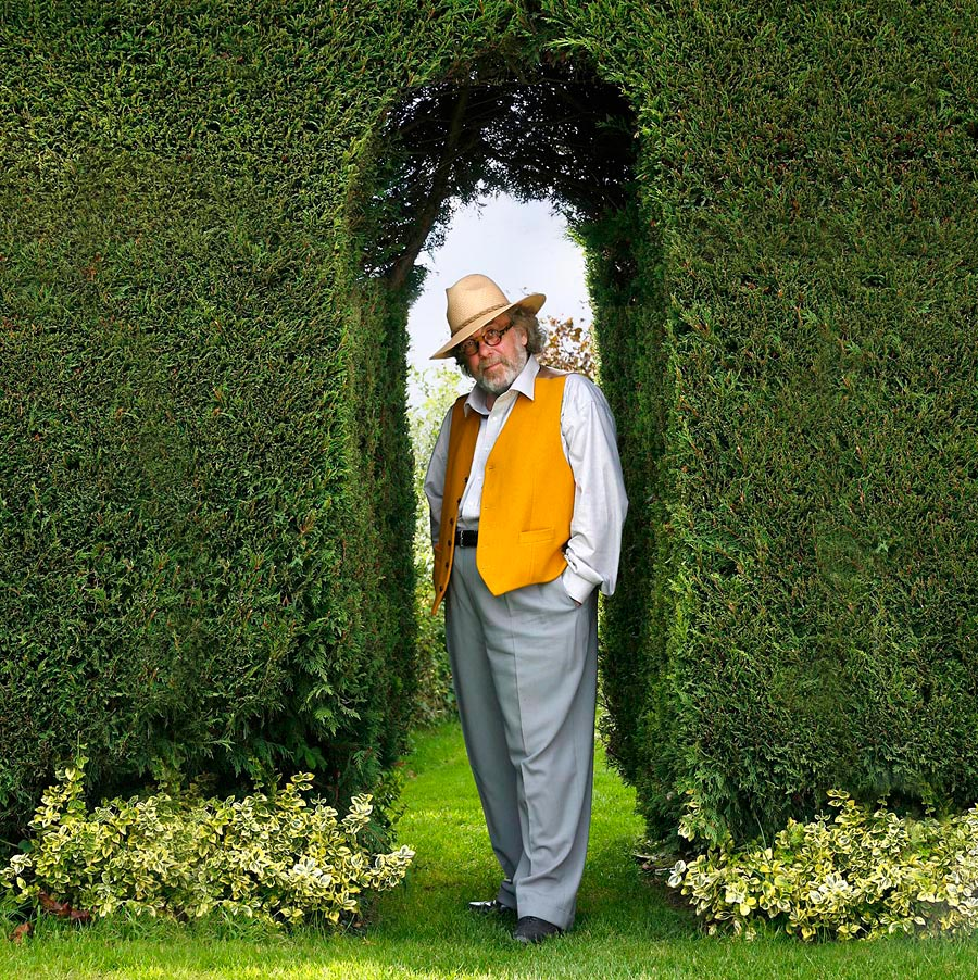 A man wearing a yellow waist coat standing in the arch of a green bush.
