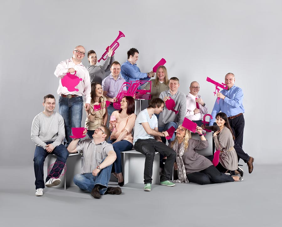 A group shot of around 15 people wearing casual clothes against a grey background. Everyone is holding flat pink plastic cut outs of objects such as  teapot.
