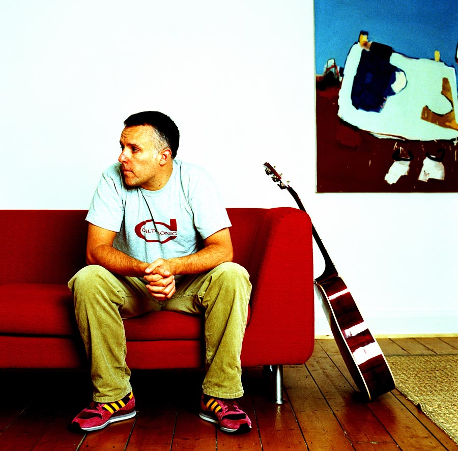 An image of a man in a tshirt and jeans sat ona  red sofa looking away. A guitar is propped against the sofa.