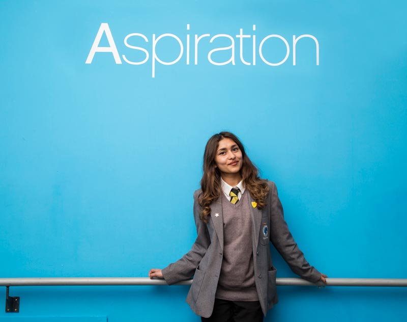 a photograph of a teenage pupil at high school under a sign saying 'aspiration'.