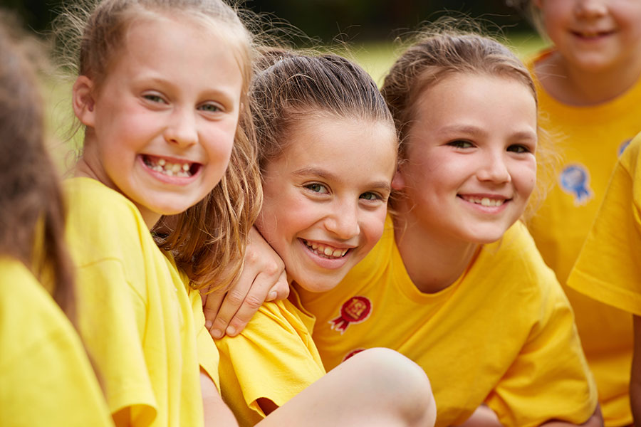 students happy and smiling watching at sports day.