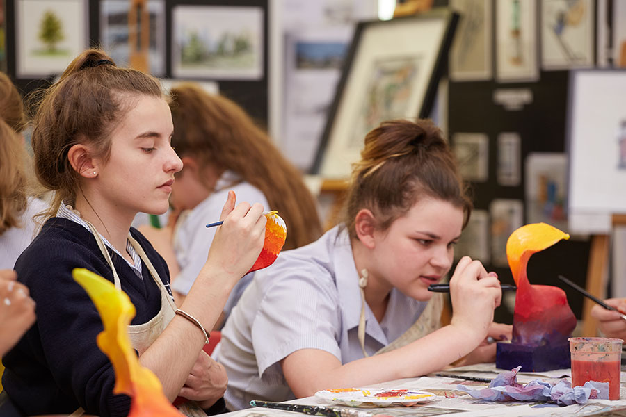 two students looking very involved in an art class.