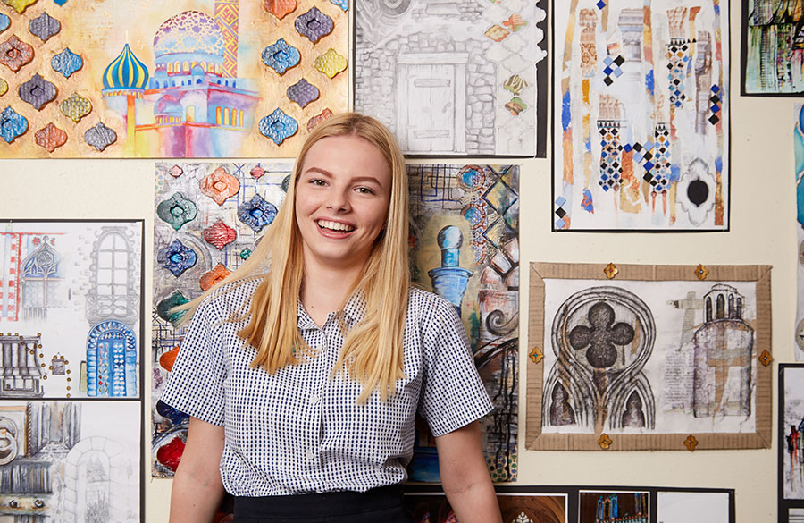 a 6th form student leaning on a wall filled with art.