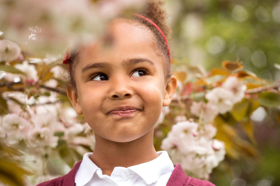 primary school child surrounded by flowers.