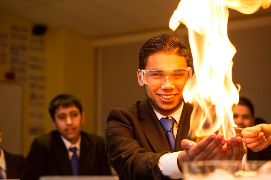 a high school student doing a science experiment with flames in his hands.
