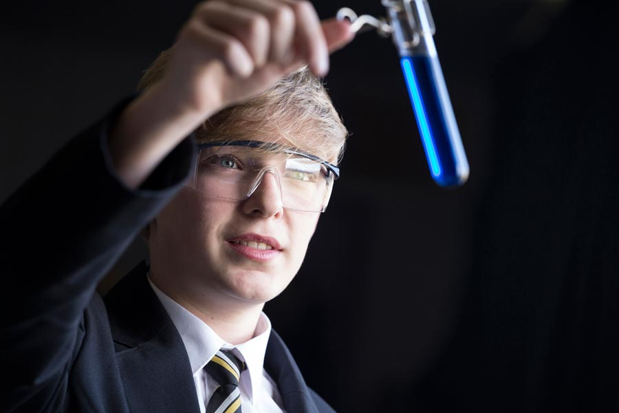 A high school student holding a test tube up to the light.