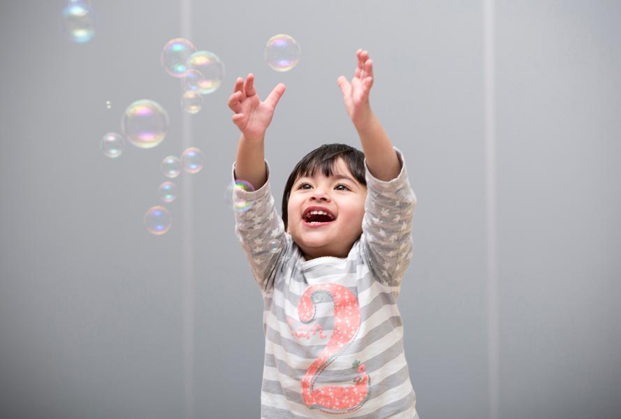 child at nursery catching bubbles