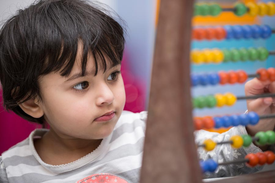 child in nursery setting playing with abacus.