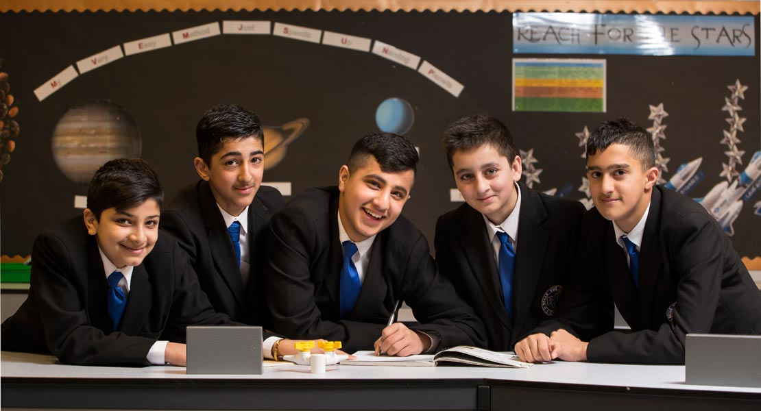 a group of 5 high school boys leaning ona table smiling to camera in a scince class room.