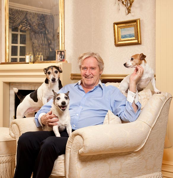 Image of William Roache sat ina chair with his three jack russel dogs.