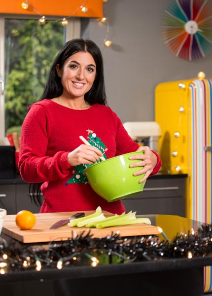 Photograph of celebrity chef Stacie Stewart in her kitchen mixing food in a bowl. Christmas theme.